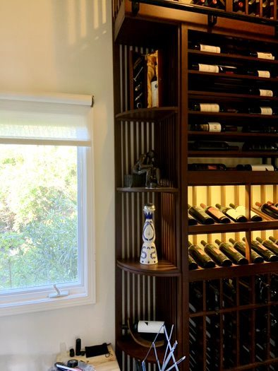 The Left Wall of This Traditional Home Wine Cellar Consists of a Curved Custom Wood Wine Rack